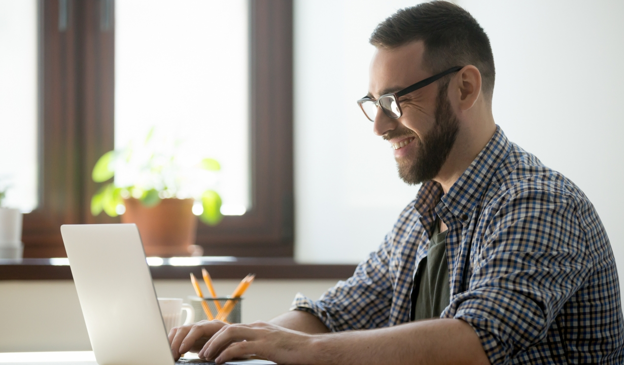 Happy male office worker smiling typing message at laptop, chatting with friends, writing positive email or consulting client online. Concept of laugher, positive work atmosphere, help and assistance